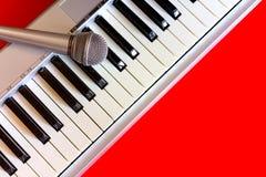 Cyfrowego pianino z mikrofonem na czerwonym bacground Zdjęcia Royalty Free