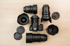Cyfrowego SLR kamera i few wymienni ręczni obiektywy Wyposażenie dla filmowania Drewniany stół obraz stock