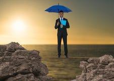 Cyfrowego złożony wizerunek biznesmen pozycja na linowym mienie dzienniczku z błękitnym parasolem wśród skały Fotografia Stock