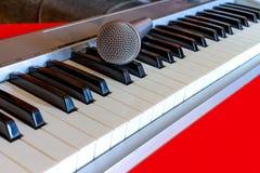 Cyfrowej fortepianowa klawiatura z mikrofonem na czerwonym bacground Obraz Royalty Free