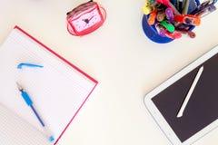 Cyfrowej pastylka nad szkolnym biurkiem między otwartą ćwiczenie książką Zdjęcia Stock