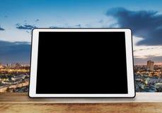 Cyfrowej pastylka, odosobniony czerń ekran na drewnianym stole z plamy miasta linii horyzontu tłem Zdjęcia Royalty Free