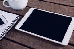 Cyfrowej pastylka, telefon komórkowy, czarna kawa i dzienniczek na drewnianym stole, Obrazy Royalty Free
