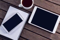 Cyfrowej pastylka, telefon komórkowy, czarna kawa i dzienniczek na drewnianym stole, Zdjęcia Royalty Free