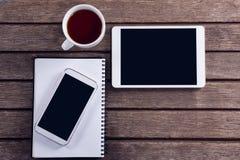 Cyfrowej pastylka, telefon komórkowy, czarna kawa i dzienniczek na drewnianym stole, Zdjęcie Royalty Free