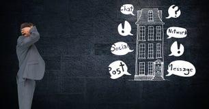Cyfrowo wytwarzający wizerunek patrzeje budynek różnorodnymi symbolami rysującymi na wa zmieszany biznesmen Obrazy Stock