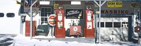 Cyfrowo zmieniający widok rocznik benzynowa stacja z starego stylu pompami i wiele staromodnymi znakami obraz royalty free