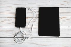 Cyfrowych przyrząda z hełmofonami na białym drewnianym tle fotografia stock