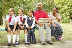 Cygańska rodzina na ławce z podręcznikami w boisku szkolnym na Wrześniu 1 Rosja obrazy royalty free