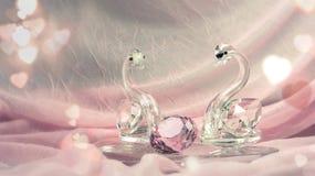 Cygnes en cristal ou en verre avec un diamant sur le tissu rose Photo libre de droits