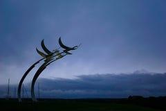 Cygnes en métal contre le ciel déprimé Images stock