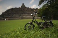 Cykel framme av den Borobudur templet i Indonesien Arkivbild