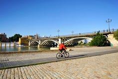 Cykel i Seville, den Guadalquivir floden och den Triana bron, Spanien arkivfoto