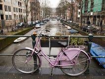 Cykel med den Amsterdam kanalen Arkivbilder