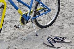 Cykel och badskor på stranden Arkivfoto