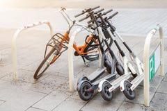 Cykel och elektriska sparkcyklar som parkeras på stadsgatan Uthyrnings- service för självbetjäninggatatransport Stads- medel för  arkivbild