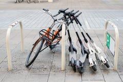 Cykel och elektriska sparkcyklar som parkeras på stadsgatan Uthyrnings- service för självbetjäninggatatransport Stads- medel för  royaltyfri foto