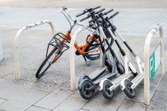 Cykel och elektriska sparkcyklar som parkeras på stadsgatan Uthyrnings- service för självbetjäninggatatransport Stads- medel för  arkivfoto