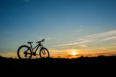 Cykel på solnedgången på ett fält Arkivbilder