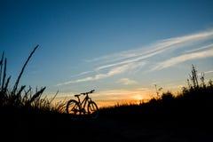 Cykel på solnedgången på ett fält Fotografering för Bildbyråer