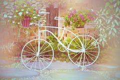 Cykel som dekoreras med blommor i trädgården Royaltyfri Bild