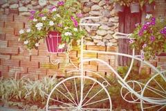 Cykel som dekoreras med blommor i trädgården Arkivbilder