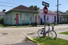 Cykel som framme parkeras på ett stopptecken av en rad av färgrika hus i en gata av staden av New Orleans i Louisiana royaltyfri fotografi