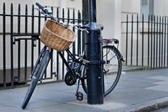 Cykel som kedjas fast till en lampost i London Fotografering för Bildbyråer