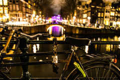Cykel som låsas på räcket av den Amsterdam kanalen vid natt Royaltyfri Foto