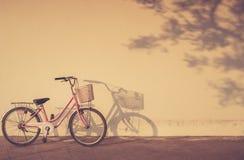 Cykel som parkeras på morgontid bredvid väggen och skuggan med a Royaltyfri Bild