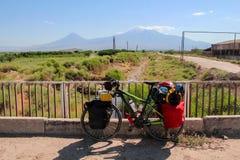 Cykel som turnerar i Armenien med Mount Ararat som bakgrund och en ström royaltyfria bilder