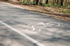 Cykelbanan parkerar in Cykeltecken på asfalt royaltyfri bild