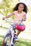 cykelflicka som ler utomhus barn Royaltyfri Foto
