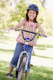cykelflicka som ler utomhus barn Royaltyfria Foton