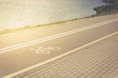Cykelgränden för övning omger med längs den sjö-/cykelgränden för övning omger med längs sjön i soluppgång royaltyfri foto