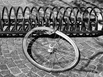 Cykelhjul på en kugge som lämnas från en stulen cykel Arkivbild