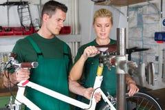 Cykelmekaniker och lärling som reparerar en cykel Arkivbild