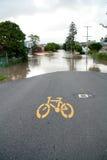 cykeln översvämmar den queensland teckengatan Arkivfoton