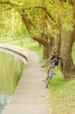 Cykeln n?ra floden in parkerar/cykeln n?ra floden parkerar in p? en solnedg?ng fotografering för bildbyråer
