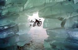 Cykeln på isen av Baikal, går med en cykel till och med vintern Baikal arkivfoto