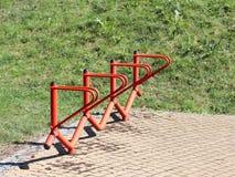 Cykeln parkerar Orange ledstänger för metall för att parkera cyklar En apparat som gör liv lättare för cyklister Lättheter för ec arkivfoto