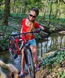 Cykeln som är tonårig med damer, cyklar i sommar parkerar Kvinnors vägcykel för att köra royaltyfri fotografi