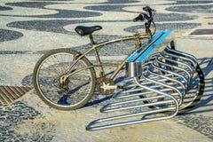 Cykelparkeringen med en gammal cykel som låsas via stor kedja på den Copacabana promenaden fotografering för bildbyråer