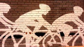 Cykelryttare som är vägg- på tegelstenväggen Arkivfoto