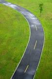 Cykelväg som går till och med en äng arkivfoto