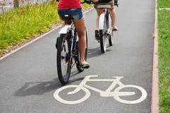 Cykelvägmärke- och cykelryttare Fotografering för Bildbyråer