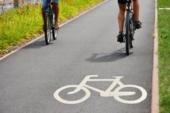 Cykelvägmärke- och cykelryttare Arkivfoto