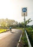 Cykelvägmärke och cykelryttare Royaltyfri Fotografi