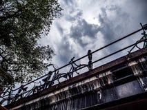 Cykla anseendet på dramatiska moln för en bro underifrån Royaltyfri Fotografi