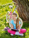 Cykla den bärande hjälmen för flickan som håller ögonen på på minnestavlaPC:n, i att cykla Arkivbild